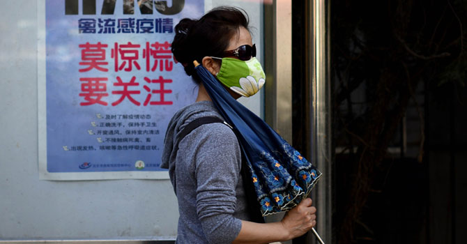 A woman wears a face mask as she walks past a poster showing how to avoid the H7N9 avian influenza virus, by a road in Beijing on April 24, 2013. — Photo AFP