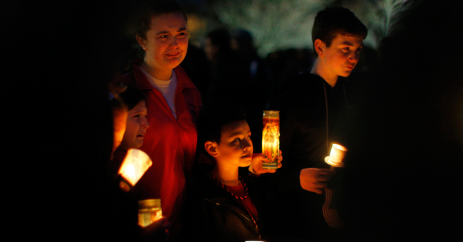 Local residents grieve during a candlelight vigil in the Dorchester neighborhood of Boston, where victim Martin Richard lived. A Little League baseball player, Martin lived in the blue Victorian house in working-class Dorchester with his parents Bill and Denise, sister Jane, 7, and brother Henry, 10. Bill Richard told the world in an email on Tuesday that his son had been killed when bombs exploded at the marathon finish line. Martin's mother and sister were seriously injured. —Photo by Reuters