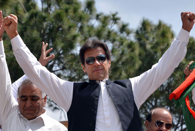 Cricket legend and chairman of Pakistan Tehreek-e-Insaaf (PTI) or Movement for Justice party, Imran Khan (C) gestures as he arrives to address supporters during a general election campaign meeting in Murree on April 29, 2013.