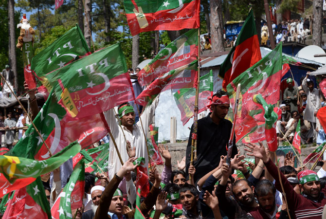 Supporters of Imran Khan wave party flags as they listen to his address.