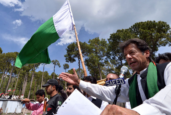 Imran Khan (R) addresses supporters.
