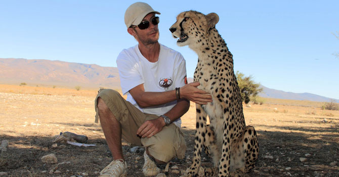 French Damien Vergnaud poses with one of his cheetahs at his private game reserve in Inverdoom, 200 kms north east of Cape Town. —Photo by AFP