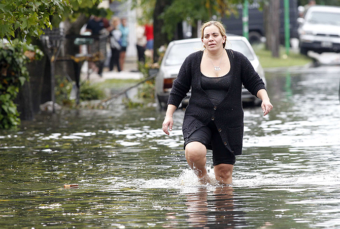 A woman wades through a street after heavy rains flooded a large part of the city, in La Plata. At least 46 people were killed in Argentina on Wednesday after a torrential downpour battered the eastern city of La Plata and forced some 2,200 people to flee their homes in search of dry ground.