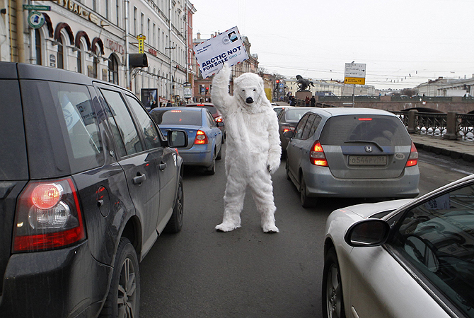 A Greenpeace activist dressed in a polar bear costume, stands amid a traffic jam holding a mock letter addressed to visiting Norwegian Prime Minister Jens Stoltenberg, near the Fontanka Canal in St. Petersburg April 5, 2013. The event aimed to draw attention to a planned joint venture between Norwegian oil company Statoil and Russian state oil giant Rosneft to explore untapped oil reserves in the Arctic, and raise awareness about the environmental impacts of oil drilling, according to organisers.