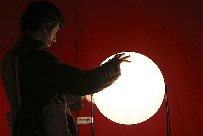 "A man touches a lamp called ""Light Sister"" on display at the Milan Design Fair, in Milan, Italy."