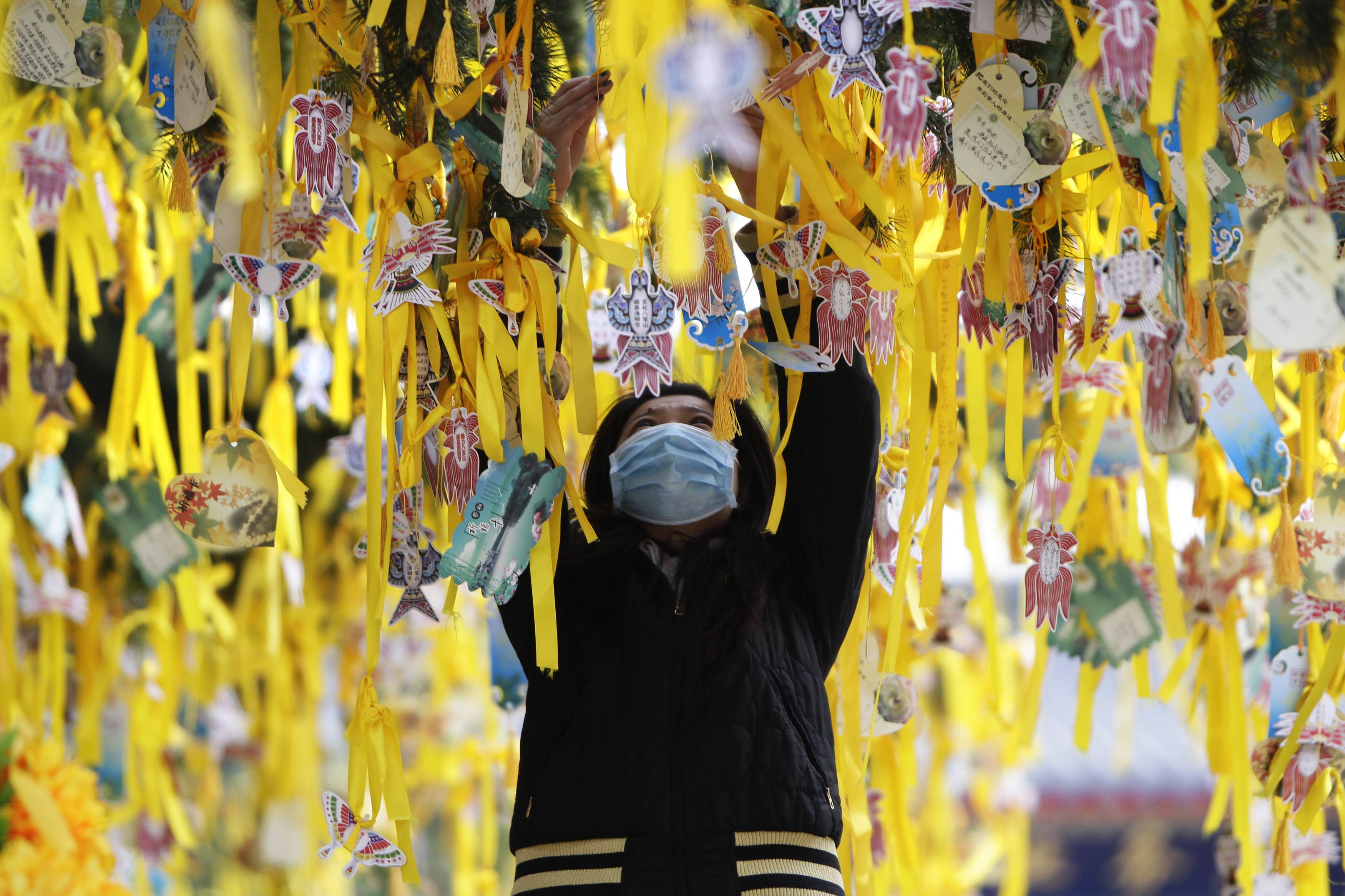 A woman hangs a yellow ribbon on a tree in remembrance of her deceased relative during Qingming Festival, or Tomb Sweeping Day, at the Babaoshan Cemetery in Beijing. The festival, which falls on April 4 this year, is a day for the Chinese to remember and honour their ancestors. A new service standard aimed at regulating the quality of China's public cemeteries has been launched recently by the Ministry of Civil Affairs to cope with the country's ageing population, according to Xinhua News Agency.