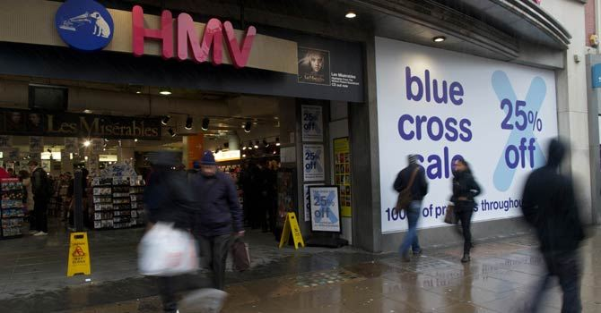 Shoppers walk past a branch of troubled music retail chain HMV on Oxford Street in central London. –Photo by AFP
