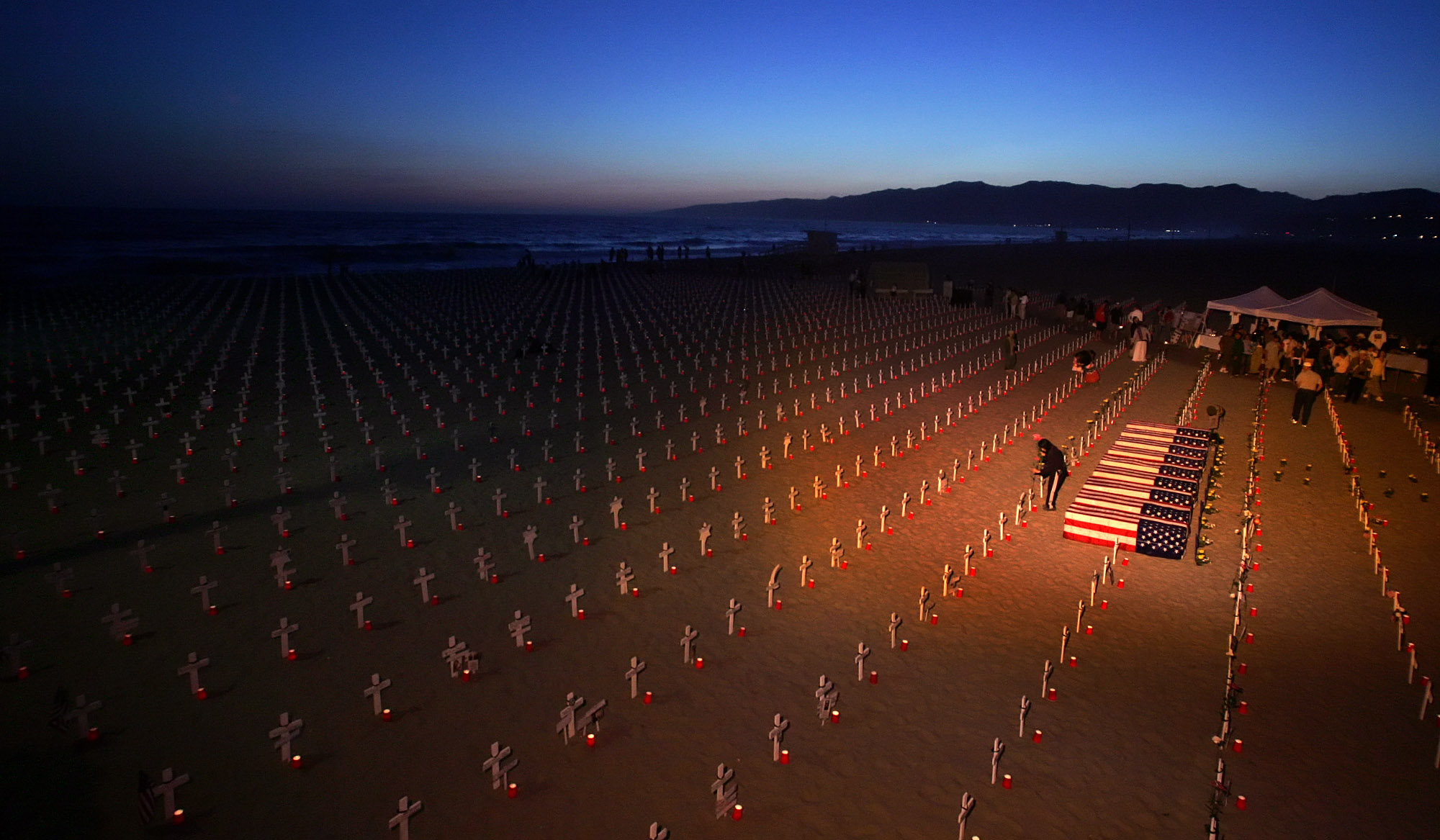 A volunteer puts flowers next to a cross at the Arlington West Iraq war memorial display on the beach next to the Santa Monica Pier in Santa Monica, Calif.