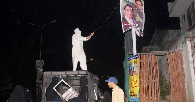 Activists from the Jamia Hafsa seminary remove posters of former president Pervez Musharraf from poles in Islamabad. -Online Photo