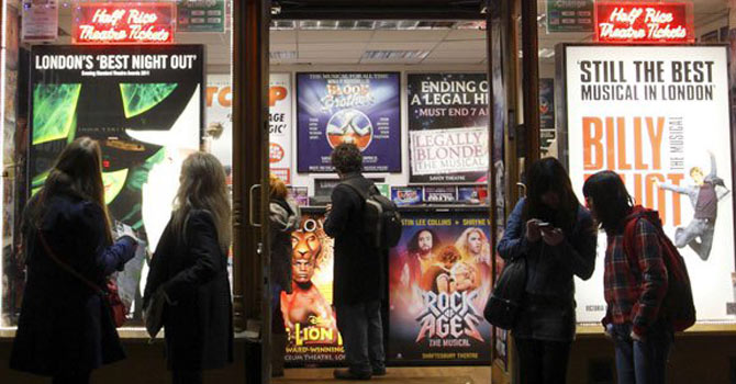 People looking at advertisement posters in the window of a box office selling discounted theatre tickets at Leicester Square in London. -Photo by AFP