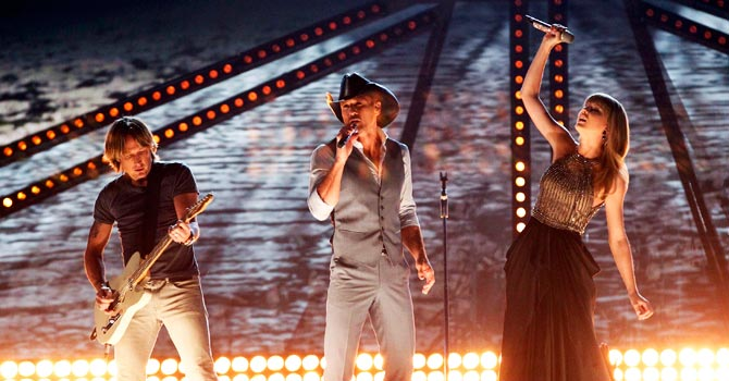 "Tim McGraw (C), Keith Urban and Taylor Swift perform ""Highway Don't Care"". —Photo by Reuters"
