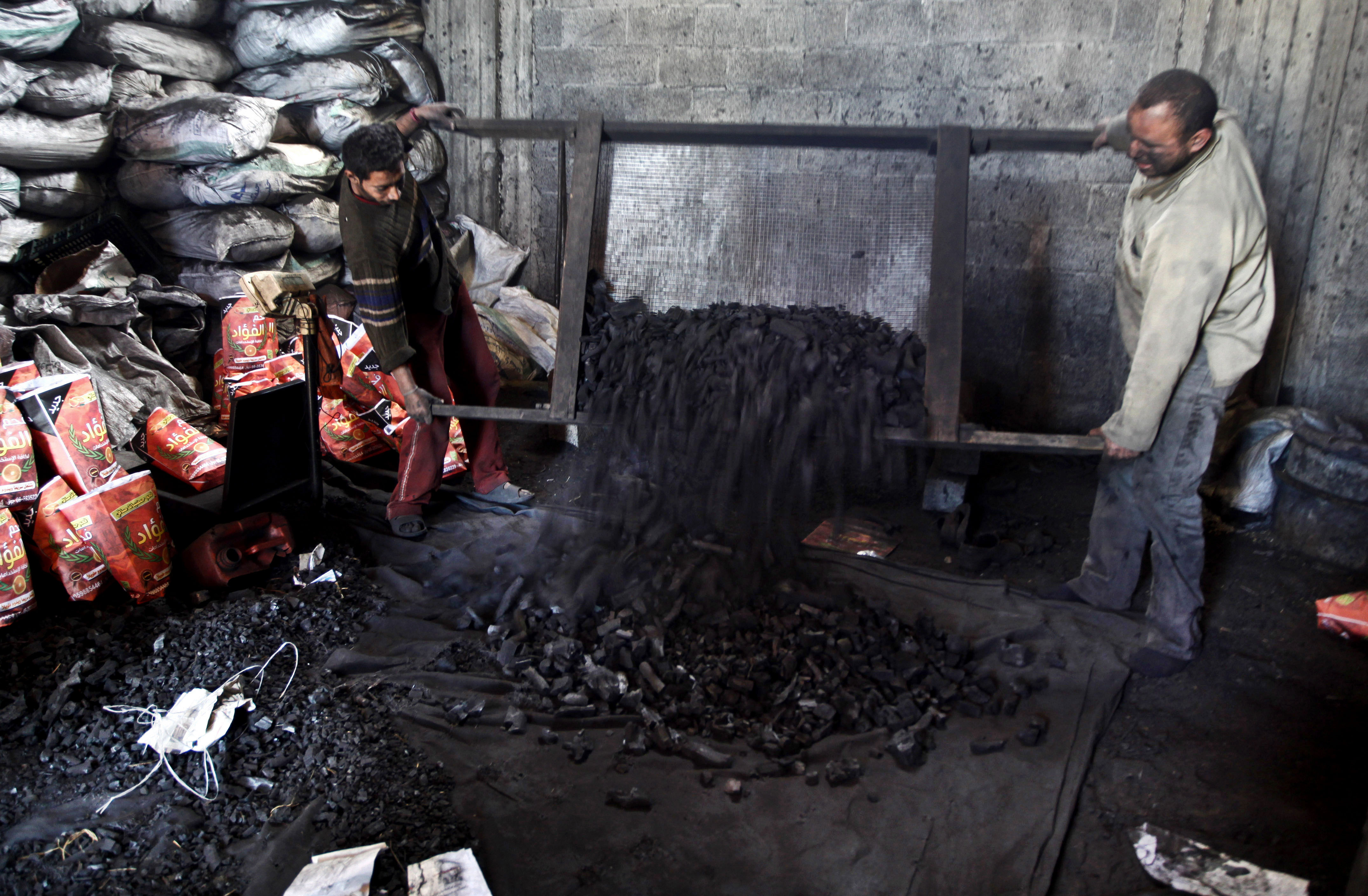 Palestinian workers sort coal to be sacked and sold, in the Jabalya refugee camp in the north of Gaza Strip.