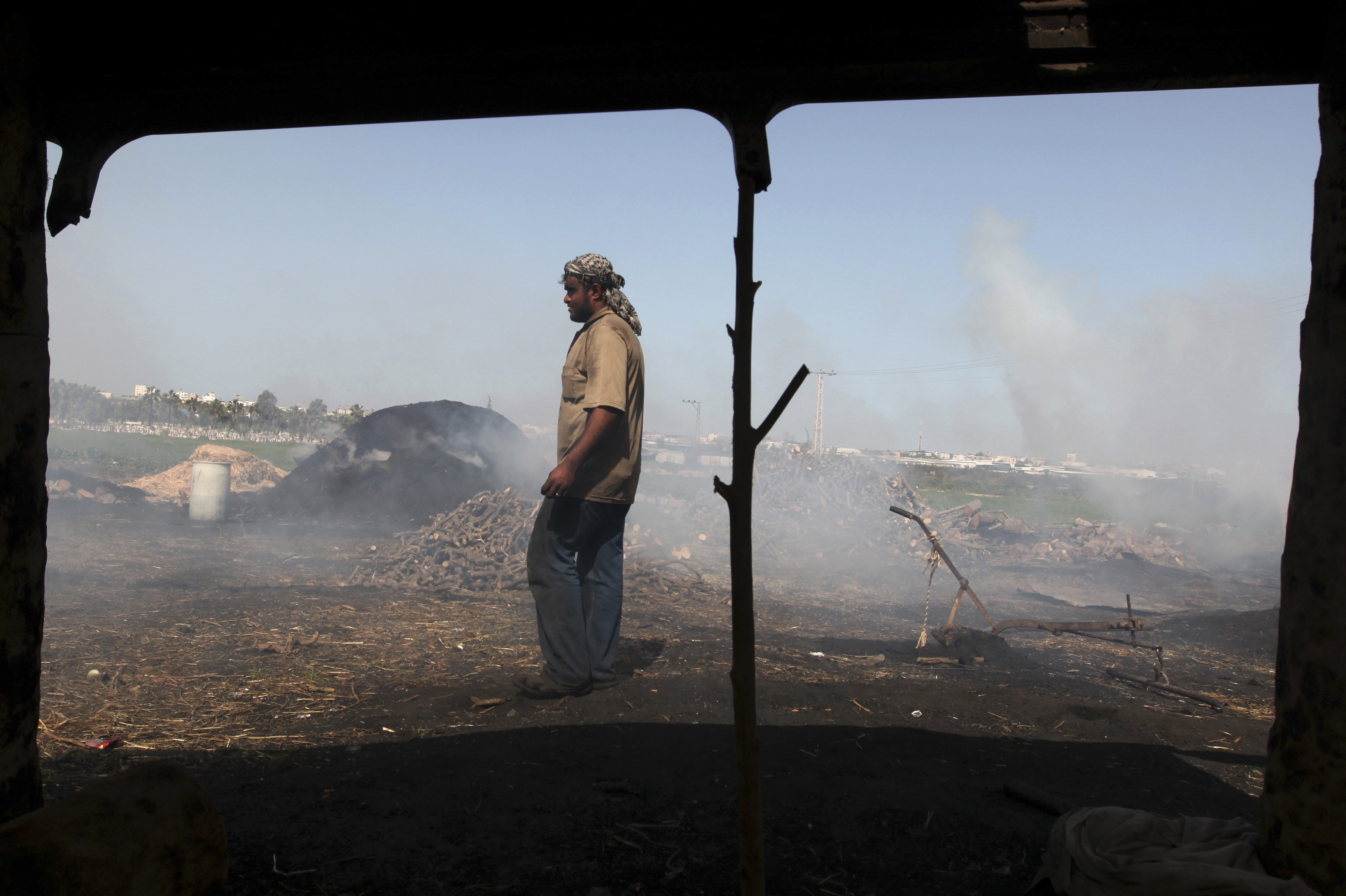 A Palestinian worker is seen from a shack as he inspects piles of coal at one of the few local charcoal manufacturing shops, east of Gaza City.