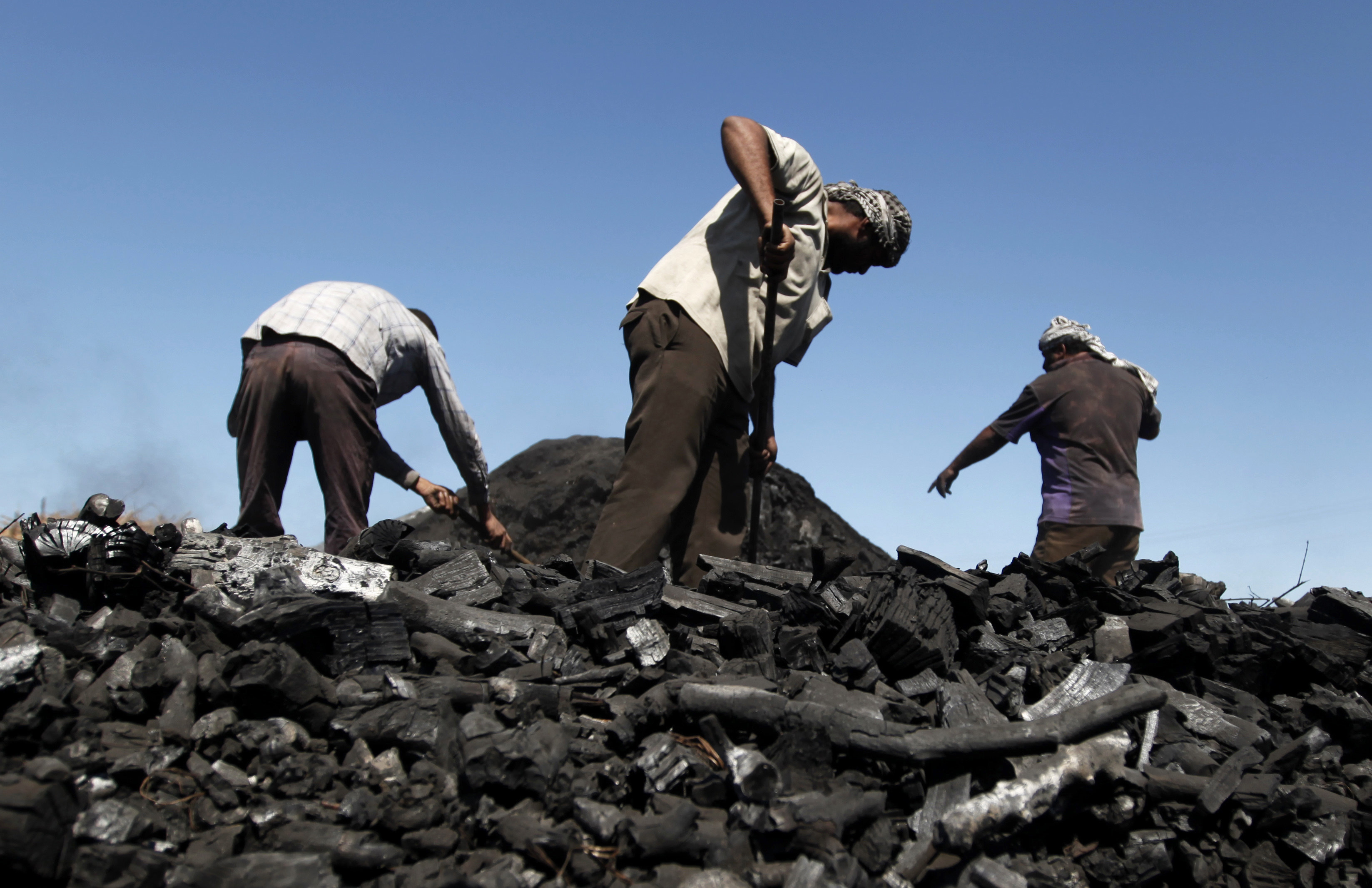 Workers remove coal from a pile at one of the few local charcoal manufacturing shops east of Gaza City.