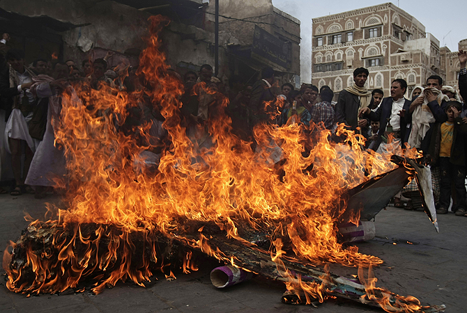 Supporters of the Yemeni al-Houthi Shia rebel group burn an effigy of a US aircraft during a demonstration to protest against US and Saudi interference in Yemen, after Friday prayer in Sanaa, Yemen.