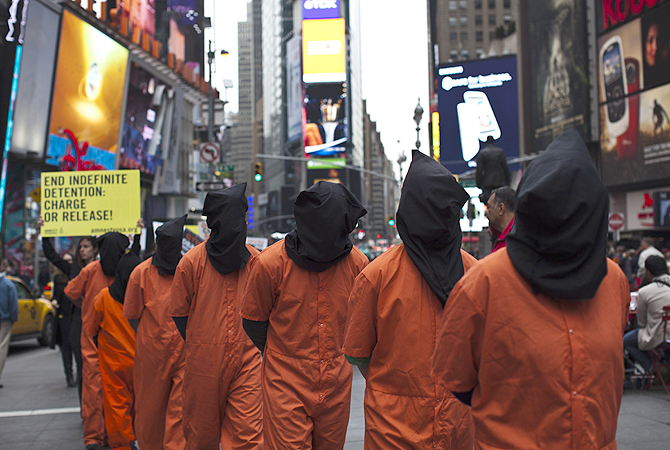 Activists dressed as prisoners demand the closure of the U.S. military's detention facility in Guantanamo Bay, Cuba while taking part in a protest in Times Square, New York.