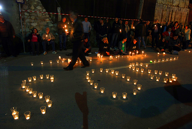 Residents of Ierissos village, Greece's northern Halkidiki peninsula, with candles make the word SOS gather during a rally outside police headquarters in the northern Greek port city of Thessaloniki. Police special forces entered the homes of two local residents early Wednesday and arrested them over their alleged involvement in a February arson attack at the nearby gold mine installations. The two men are detained in police headquarters of Thessaloniki as the local residents demand their release and protest agains