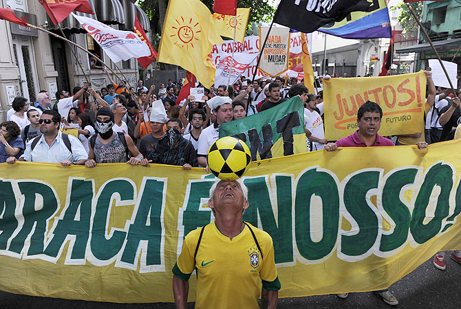 "Activists protest in front of the Guanabara state government's palace against the privatization of the Mario Filho ""Maracana"" stadium in Rio de Janeiro, Brazil. Bidding for the privatization of Rio's iconic Maracana stadium was to go ahead as planned Thursday after a local court rejected an appeal to block the process.  Maracana, which was built for the 1950 World Cup, is undergoing extensive renovation at a cost of 430 million dollars to host four Confederations Cup matches in June as well as seven World Cup games"