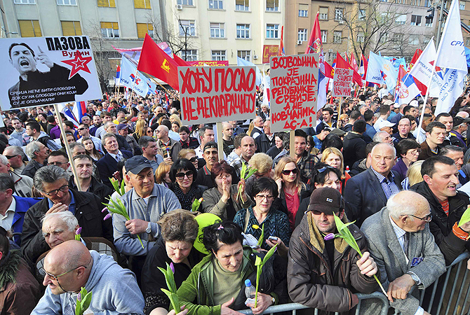 "People wave flags and hold banners during a protest in Novi Sad. Thousands of supporters of Serbia's ruling parties rallied against the leadership of the country's autonomous Vojvodina province on Friday, against a backdrop of rising political tension over the northern region. The banners read, ""I want a job, not a declaration"" (C) and ""Vojvodina is a Serbian province, not a wallet of DS (Democratic Party)"" (centre R)."