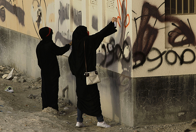 "Bahraini women spray anti-government graffiti during a march in A'ali, Bahrain. Old political graffiti includes ""steadfast."" Thousands of anti-government demonstrators in Bahrain have joined a march that included breakaway protests against the scheduled Formula One race later this month."