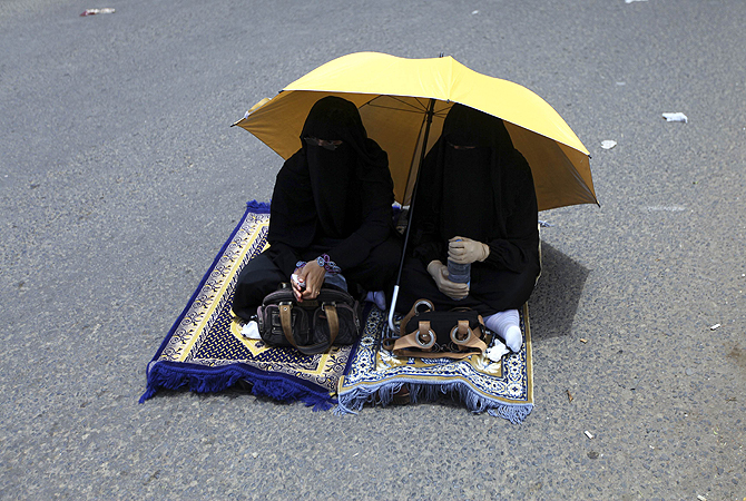 Women sit on street to pray during Friday prayers at a weekly rally on Siteen Road in Sanaa. Pro-democracy protesters at the rally showed their support for the recent pro-military decisions by Yemen's President Abd-Rabbu Mansour Hadi. Hadi removed the commander of the elite Republican Guard, a powerful political foe, from the military on Wednesday, state television reported, in an apparent move to unify the divided armed forces under his own control.