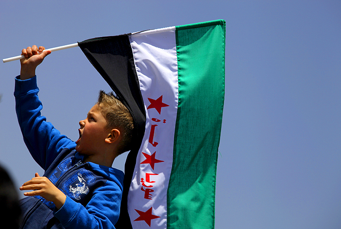 "A boy waves the Syrian revolutionary flag as protester chant anti-Bashar Assad slogans and pro-Jabhat al-Nusra and Free Syrian Army slogans, in front of the Syrian embassy, in Amman, Jordan. The Arabic writing on flag reads ""free Syria."" With a fresh influx of weapons, Syrian opposition fighters have made significant gains in the past weeks, particularly in the southern province of Daraa, where rebels have been advancing in the region between the Jordanian border and the capital, Damascus."