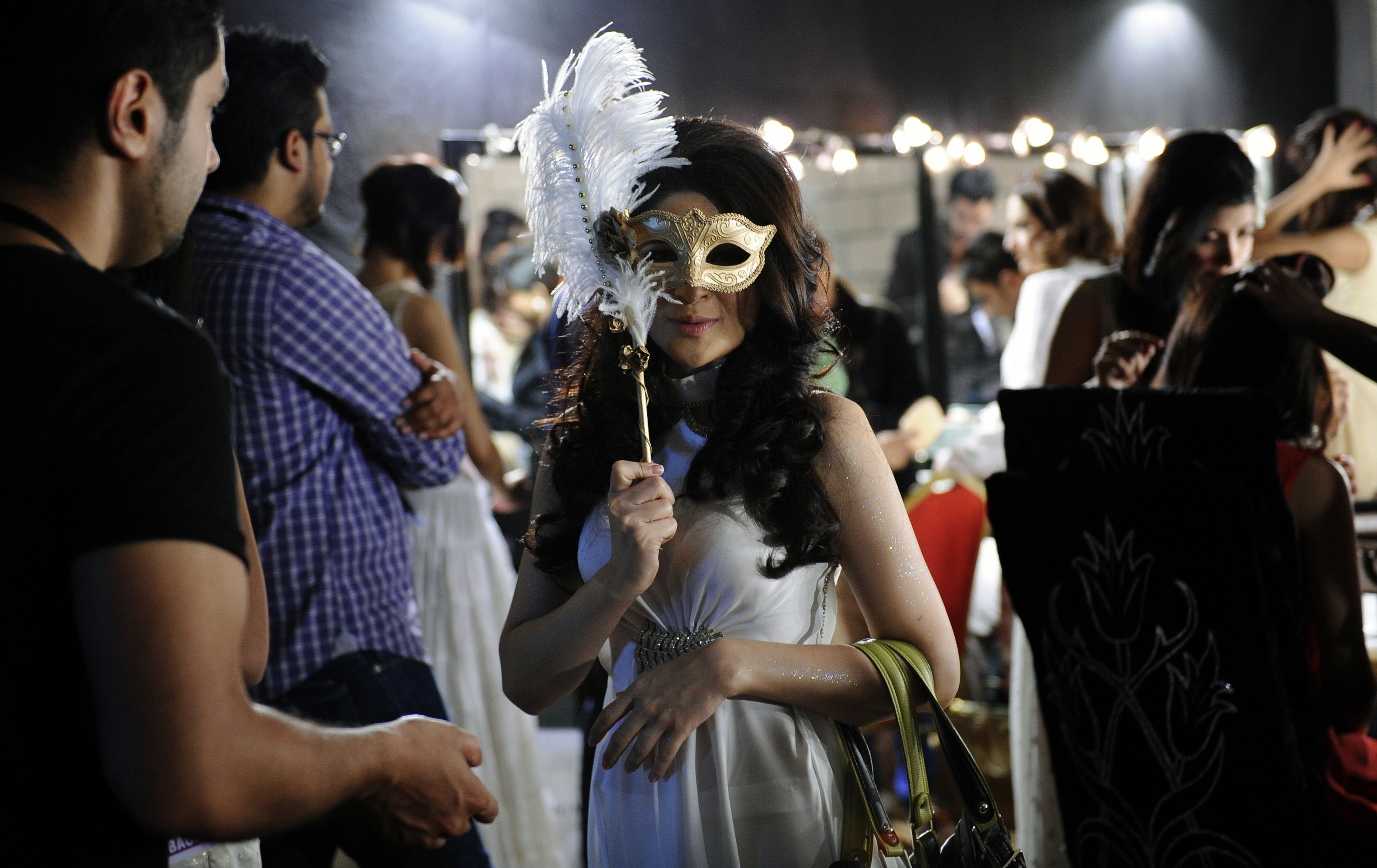 Model Ayesha, wears a mask as part of the hair and makeup show as she prepares to take to the catwalk on the first day of the Bridal Couture Week in Karachi April 19, 2013. The event will be held from April 19 to 21. — Reuters Photo