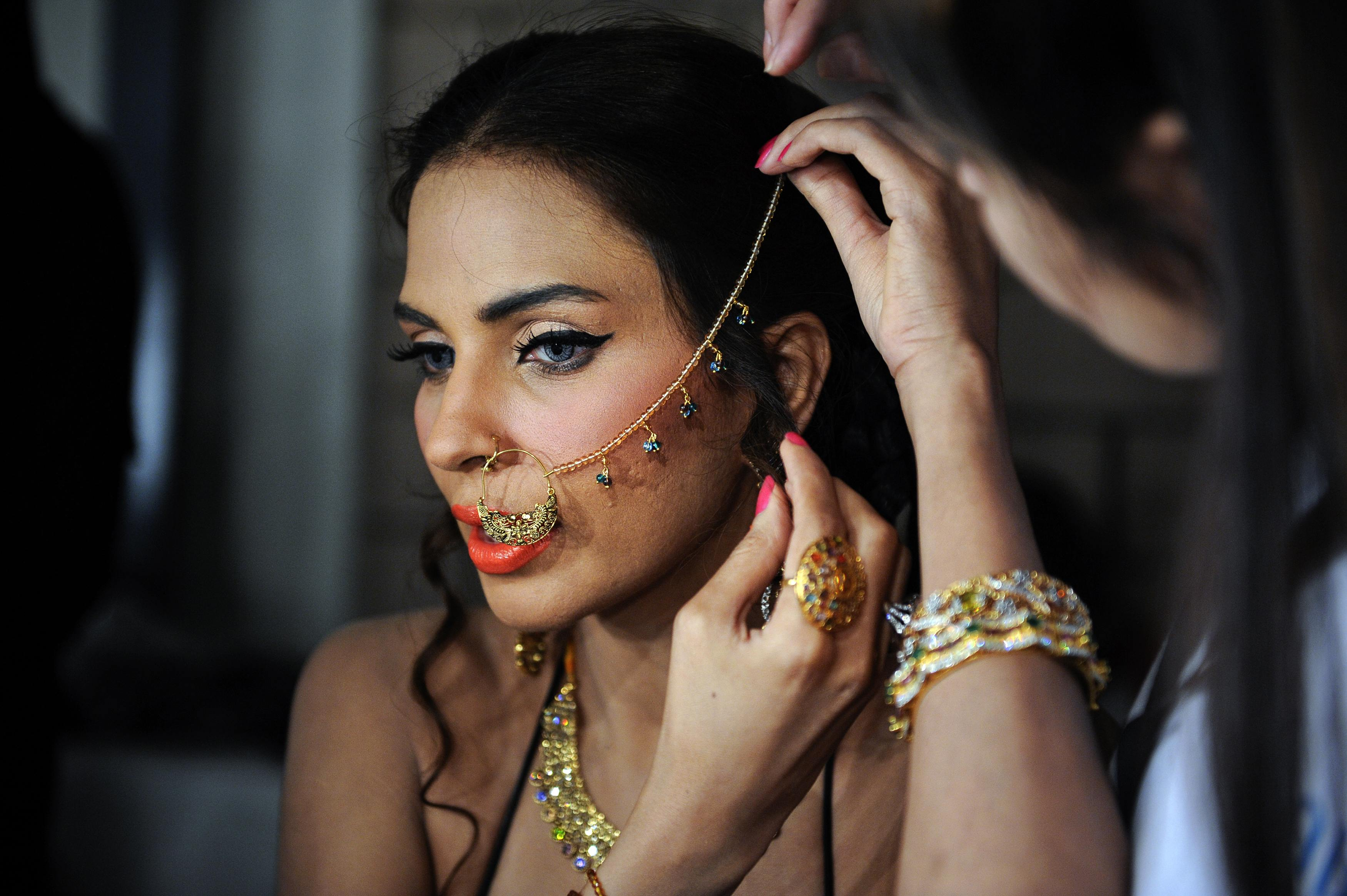 Model Fauzia wears traditional bridal jewellery as she prepares to take to the catwalk on the first day of the Bridal Couture Week in Karachi April 19, 2013.— Reuters Photo