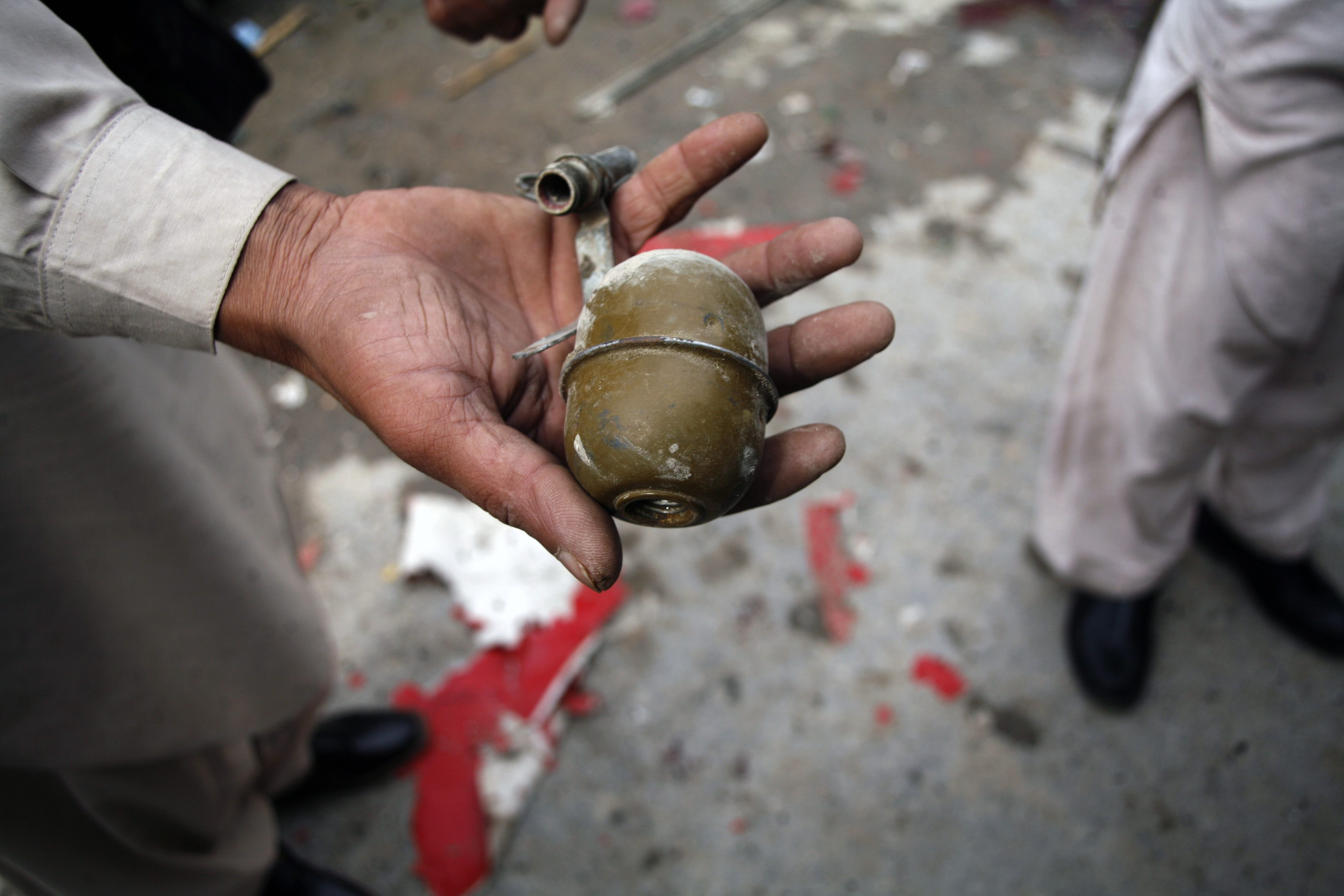 A security official shows a detonated grenade found at the site of a bomb attack in Quetta April 24, 2013. The bomb blast, which happened near a private hospital, injured at least 13 people, including two children in the city's Satellite Town area on Wednesday, according to local media. The explosive device, detonated with a remote control, was planted on a bicycle, the news report said.  — Reuters Photo