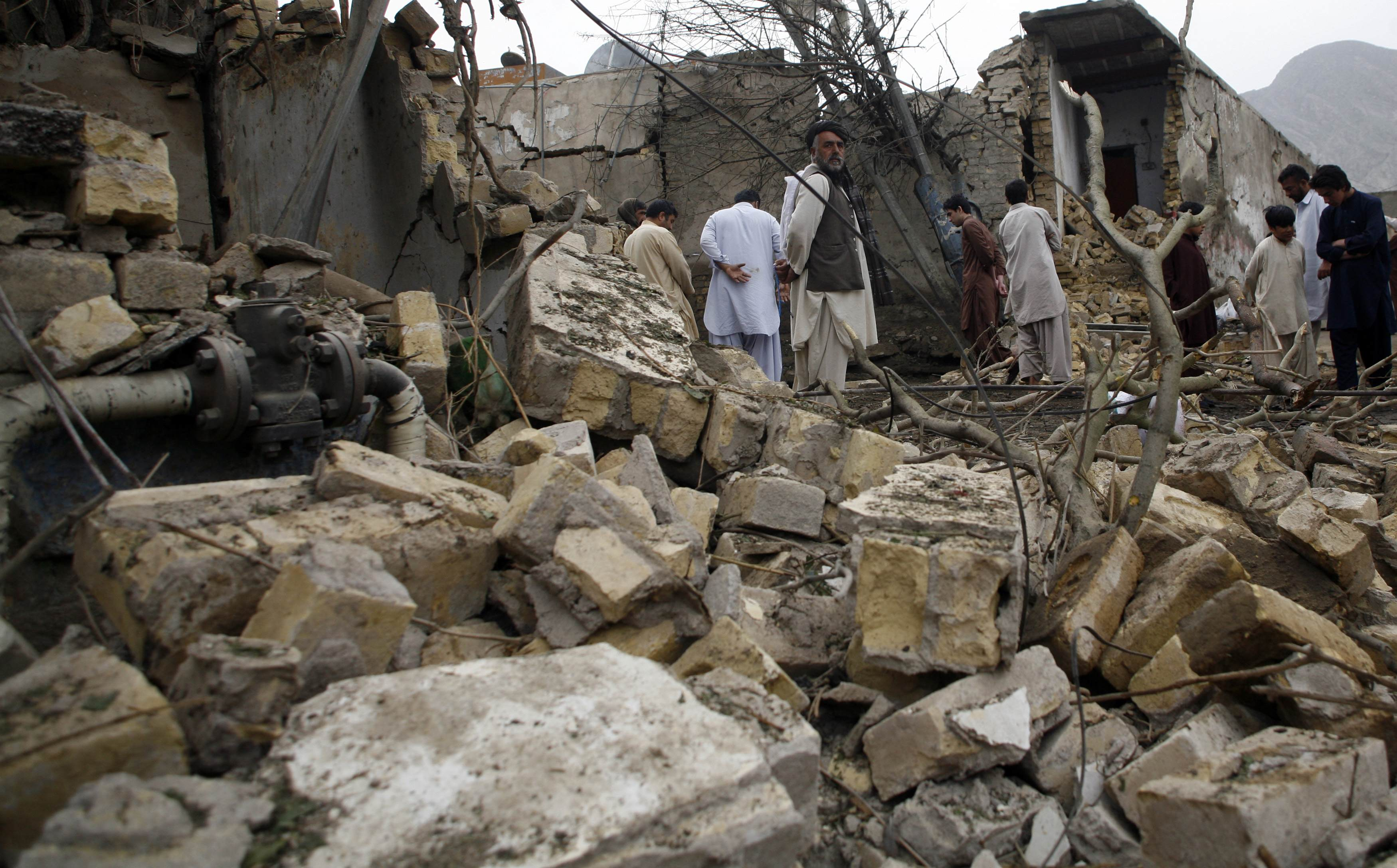 Residents stand among rubble and debris at the site of Tuesday's bomb attack in Quetta April 24, 2013. A prominent leader of Pakistan's ethnic Hazara minority narrowly escaped the suicide attack that killed six people on Tuesday, underscoring the growing threat militants pose to secular politicians in the run-up to next month's general elections. The blast in Quetta was the worst attack since a series of bombings in the city at the start of the year killed almost 200 people, briefly drawing global attention to a gr