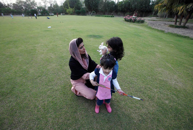 Former Pakistan Foreign Minister Hina Rabbani Khar plays with her daughter and niece in the lawns of her residence after an interview with Reuters in Muzaffargarh in Punjab province April 9, 2013.