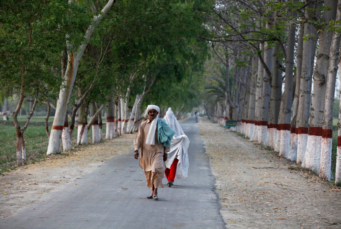 People walk on the road that leads up to the residence of Hina Rabbani Khar.