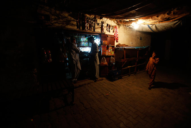 People are seen near a small grocery store in a narrow street which leads up to the house of Jamshed Dasti.