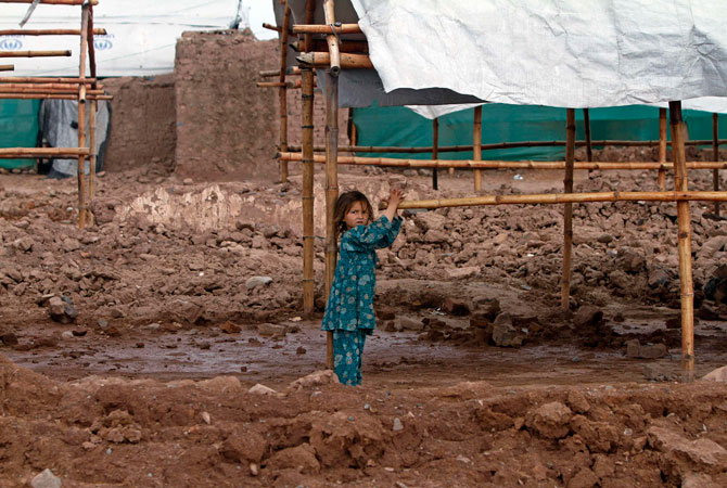 An internally displaced girl Ayesha, 4, whose family fled the military operations in Khyber Agency, plays outside her family tent at the UNHCR Jalozai camp in Pakistan's northwest Khyber-Pakhtunkhwa province.