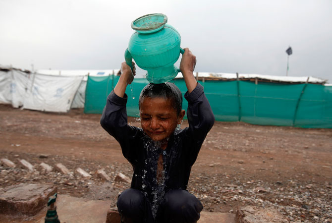 Internally displaced boy Asif, 4, whose family fled the military operations in Khyber Agency, cools himself off at the UNHCR Jalozai camp.
