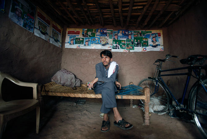 Internally displaced man Sakhi jan Afridi, 30, who fled the military operations in Khyber Agency, waits for his turn in a barber shop decorated with election posters of contesting candidates at the UNHCR Jalozai camp.