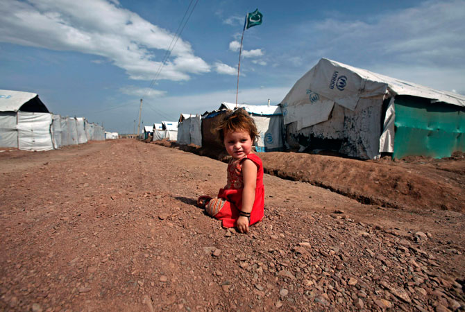 Internally displaced girl Laiba, 1, whose family fled the military operations in Khyber Agency, sits outside her family tent while a Jamaat-e-Islami party flag flies in the background at the UNHCR Jalozai camp.