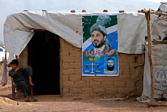 Internally displaced man Jabbar, 18, sits beside an electoral poster of Jamat-e-Islam candidate Shah Faisal Afridi at the UNHCR Jalozai camp.