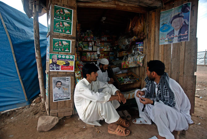 Internally displaced people, who fled military operations in the Khyber Agency, sit beside a shop decorated with election posters of contesting candidates, at the UNHCR Jalozai camp.