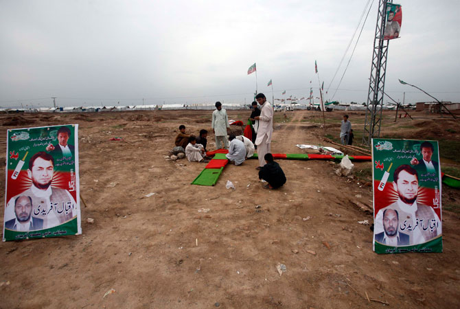 Internally displaced people and supporters of Haji Iqbal Afridi, Pakistan's Tehreek-e-Insaf (PTI) candidate for the upcoming elections, prepares to set up a campaign office at the UNHCR Jalozai camp.