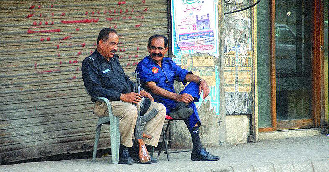 A policeman and a private security gaurd sitting on chairs on footpath along Burns Road chit-chatting on Saturday. —White star