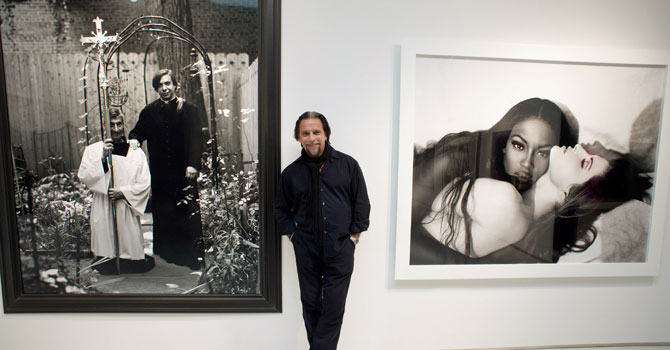"Photographer Sante D'Orazio poses between two of his photographs at Christie's in New York. D'Orazio's photos are part of ""Photographs Week at Christie's"". —Photo by AFP"