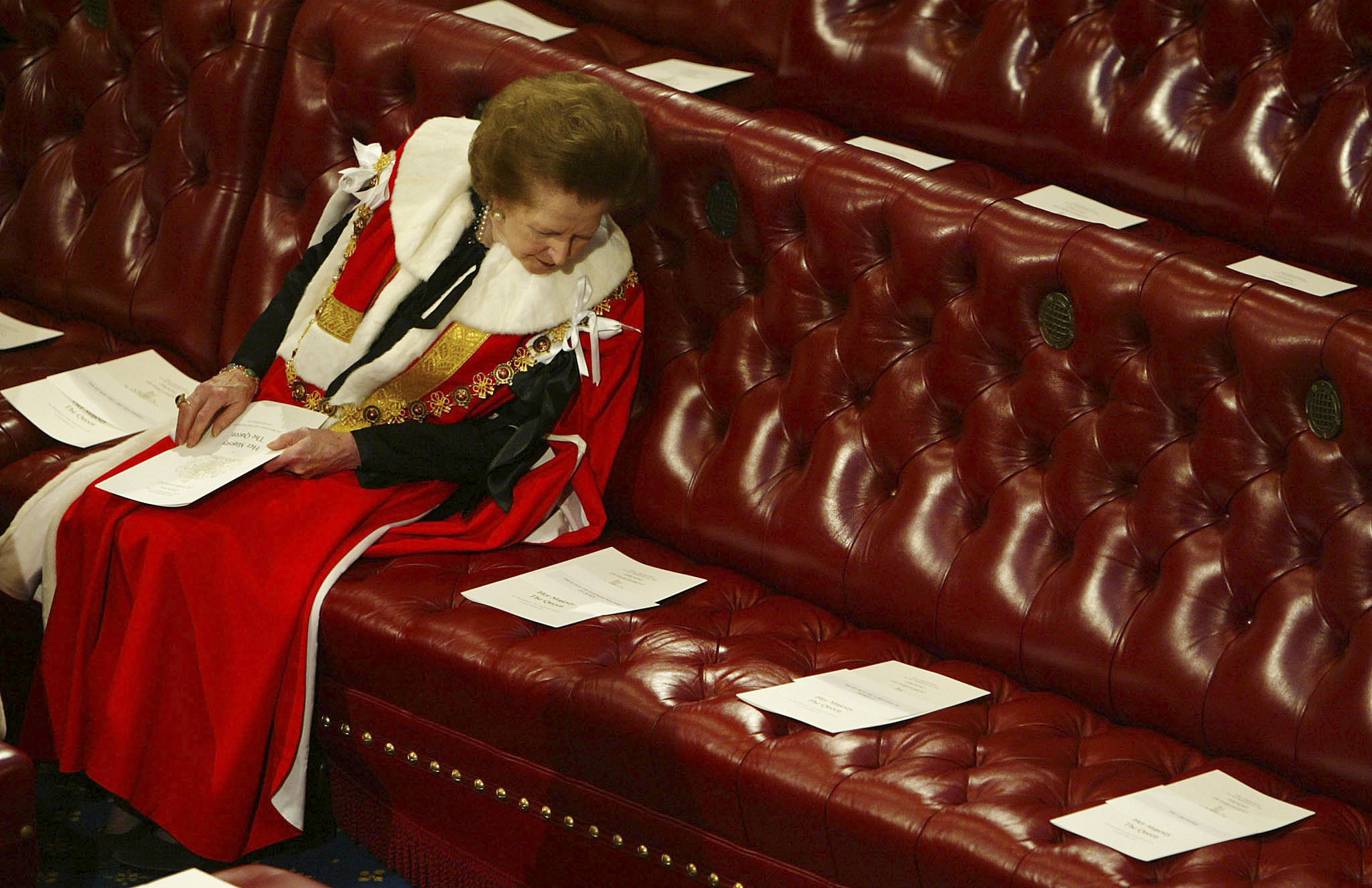 Britain's Baroness Thatcher reads the order of service surrounded by empty seats as she waits for Queen Elizabeth to deliver her speech at the State Opening of Parliament in the House of Lords in London in this November 13, 2002 file photo.