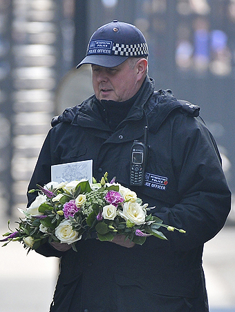 A Metropolitan Police officer carries flowers into Downing Street in London.  The Queen and her husband, the Duke of Edinburgh, will attend the funeral of former prime minister Margaret Thatcher, which is likely to be the grandest funeral for a British politician since Churchill's state funeral in 1965. Though accorded full military honours, Thatcher did not want a state funeral. She will be cremated.