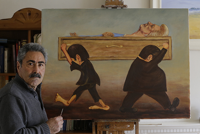 "Political painter Kaya Mar, 56, poses for a photographer with his latest painting depicting the funeral of former British Prime Minister Margaret Thatcher at his home in London. According to the artist, the scene is depicted by a member of the working class, left, that was affected by her policies, and carries her coffin one way, while a member of the finance sector, right, who benefited, carry it the other way, depicting the divisions she created in the society. Thatcher, the combative ""Iron Lady"" who infuriated E"