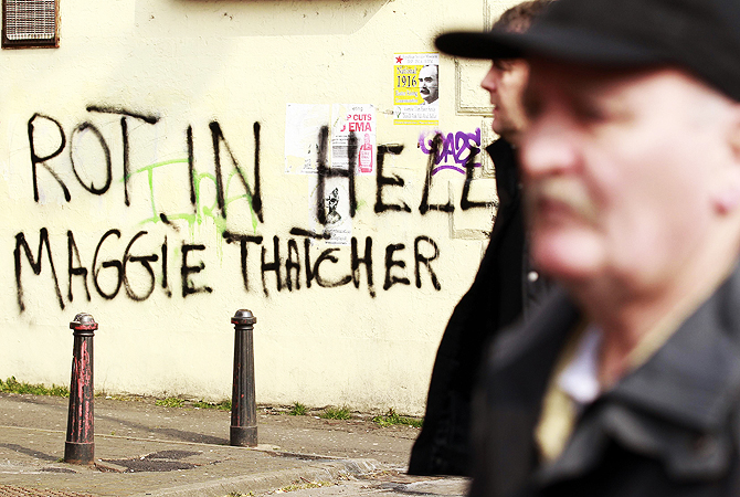 Men pass graffiti daubed on a wall referring to the death of former prime minister Margaret Thatcher, on the Falls Road in west Belfast.