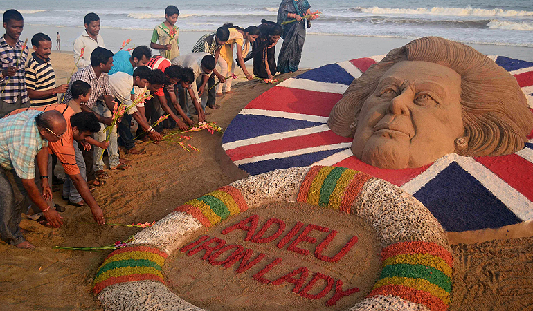 "Indians pay tribute beside a sand sculpture of former British prime minister Margaret Thatcher, made by sand artist Sudersan Pattnaik, at the Golden Sea beach in Puri, about 65 kilometers from the eastern Indian city of Bhubaneswar. Britain will hold the funeral of former prime minister Margaret Thatcher on Wednesday April 17 with Queen Elizabeth II leading the mourners, officials said, as the country wrestled with deeply divided views of the ""Iron Lady."""