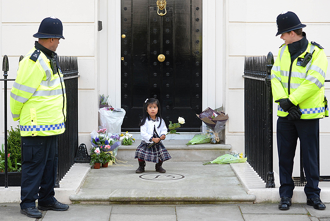 British police look on as a girl holds a rose amid floral tributes at the home of former British Prime Minister Margaret Thatcher in central London. British lawmakers will interrupt their holidays for a special session of parliament on April 10 to debate the legacy of Margaret Thatcher, who died on April 8 aged 87 after suffering a stroke.