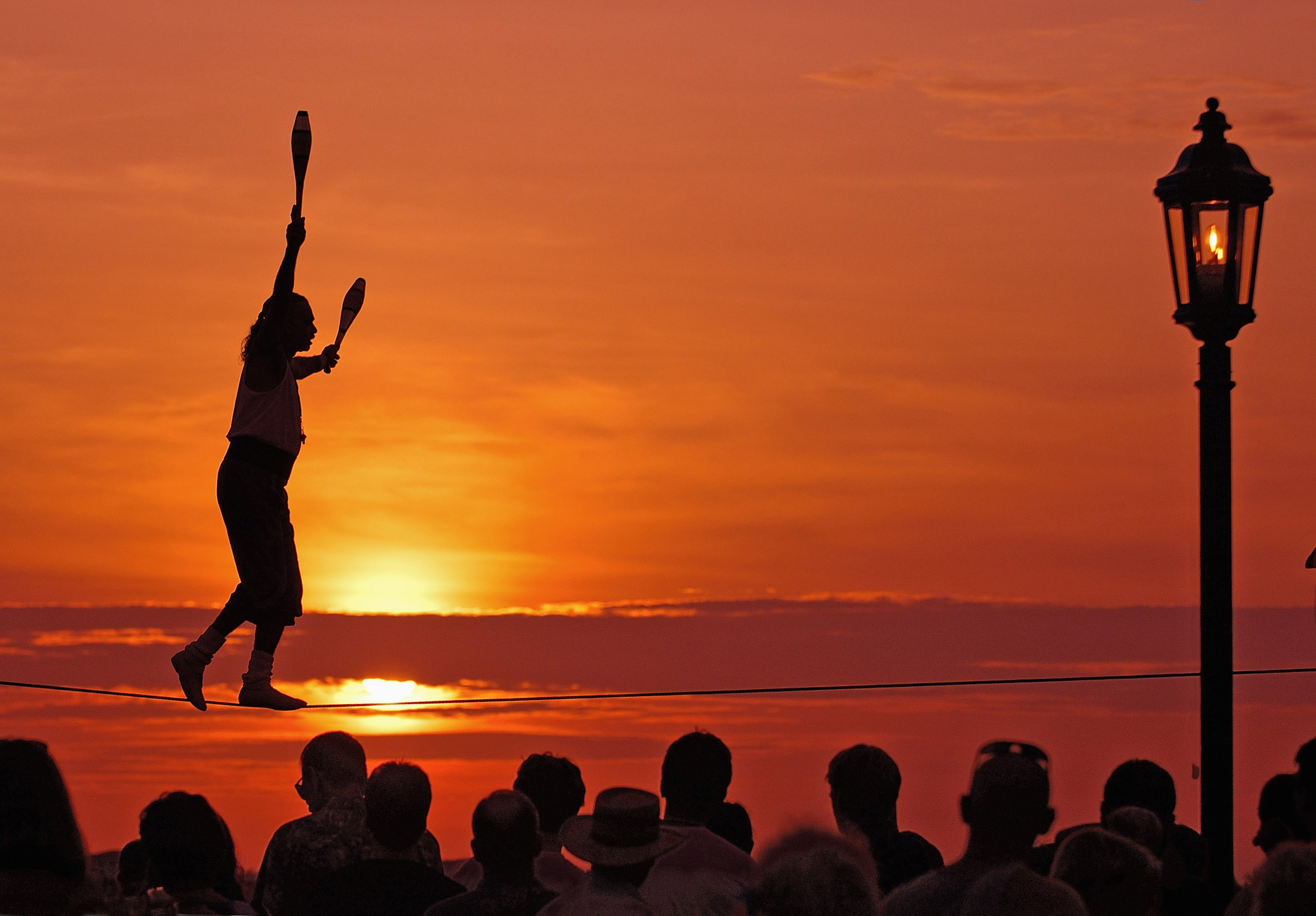 Busker Will Soto walks a tightrope at the sunset celebration in Key West, Florida, in this file photo taken in 2007. The sunset celebration at Mallory Square is a daily ritual for visitors to this subtropical island at the bottom of the Florida Keys. The Florida Keys are the end of the road, where the legendary US Route 1 stops for the ocean at mile zero, a classic American road trip.