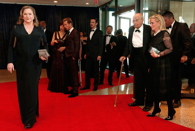 Actress Kathleen Turner (L) poses for the cameras as US Representative John Dingell (D-MI) (2nd R) and his wife Debbie Dingell (R) arrive on the red carpet at the annual White House Correspondents' Association dinner in Washington April 27, 2013.